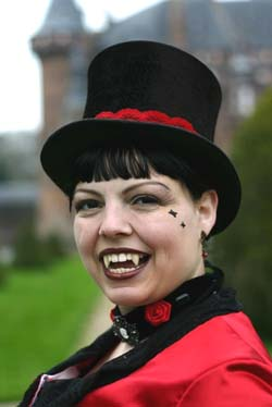 A snazzy smiley vampiress enjoys an event at a castle.